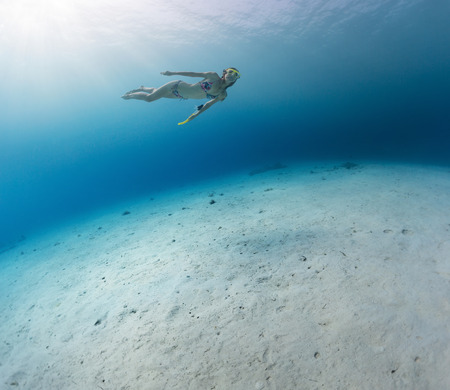 skin diving: Young lady skin diving in tropical sea over sandy bottom