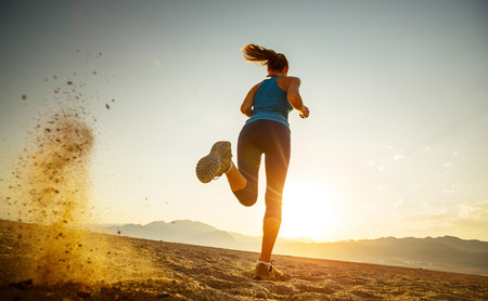 back ground: Young lady running in the desert at sunset Stock Photo