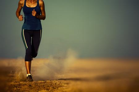사막에서 실행중인 젊은 아가씨. 가장자리는 발에 초점을 흐리게 스톡 콘텐츠