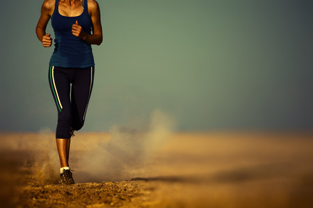 road runner: Young lady running in the desert. Edges are blurred focus on the foot
