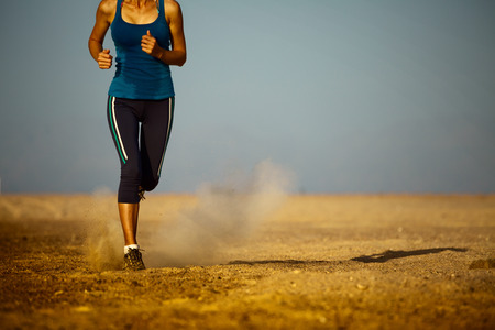 perspiration: Young lady running in the desert Stock Photo