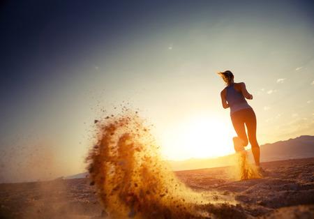 夕暮れ砂漠で実行されている若い女性