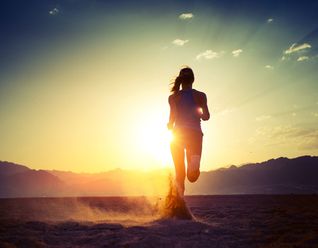 Young lady running in the desert at sunset Stock Photo