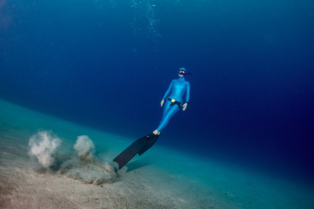 free diver: Free diver ascending from the sandy bottom
