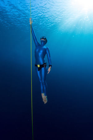 Lady free diver ascending along the rope. Free immersion discipline