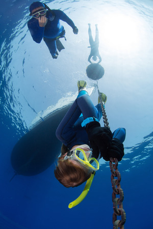 free diver: Lady free diver descending along the metal chain using his hands, free immersion. Safety buddy descending close to the athlete