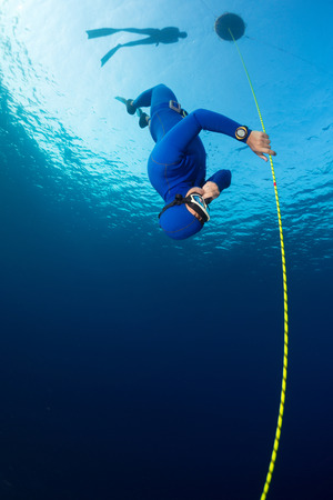 immersion: Free diver decsending along the rope. Free immersion discipline Stock Photo