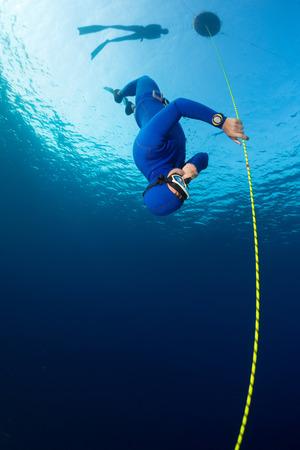 Mergulhador livre decsending ao longo da corda. Disciplina imers