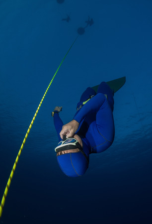 Free diver falling into deep darkness along the rope Stock Photo