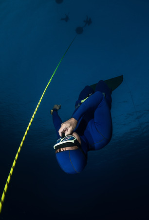 free diving: Free diver falling into deep darkness along the rope Stock Photo