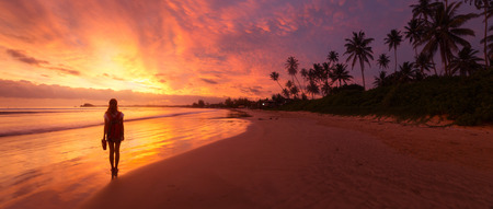 Dame, die auf dem nassen Sandstrand bei Sonnenuntergang