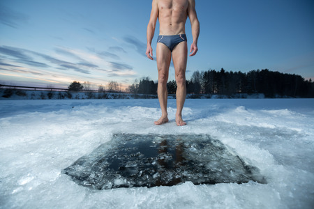 젊은 남자가 얼음 구멍으로 서서 겨울 물에서 수영을 준비
