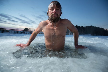 frozen lake: Young man bathing in the ice hole Stock Photo