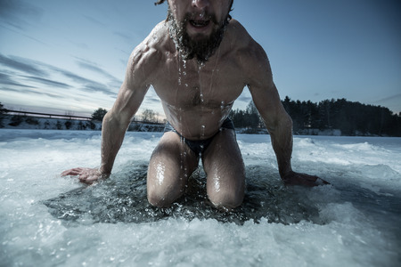 plunge: Young man bathing in the ice hole Stock Photo