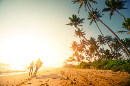 Couple walking on the sandy beach with palm trees