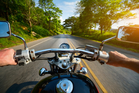 rider: Driver riding motorcycle on an asphalt road through forest