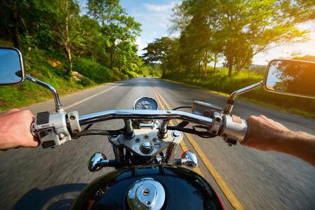 Motorista montando motocicleta em uma estrada de asfalto através da floresta