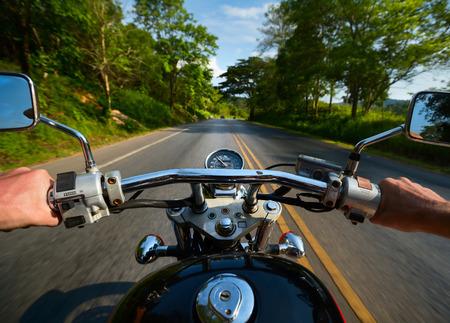 森の中のアスファルトの道路のバイクに乗ってドライバー 写真素材