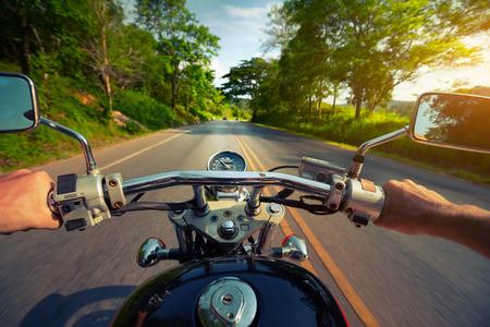 rider: Conductor montar motocicleta en una carretera de asfalto a trav�s del bosque Foto de archivo
