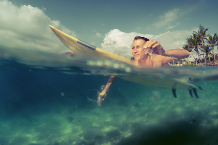 surfer: Young lady paddling on the surf board