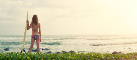 surf girl: Surfer girl standing with board on the green beach