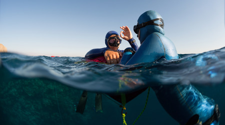 Split shot of two free divers training in sea with buoy Stock Photo