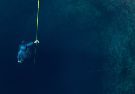 free diver: Free diver ascending along the rope Stock Photo