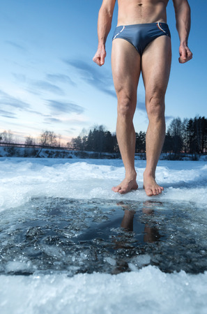 strength therapy: Young man standing by ice hole and ready to swim in the winter water