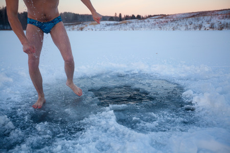 Young man walking near the ice hole after recreational swim photo