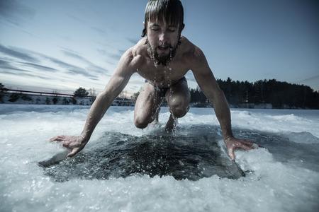 frio: Ba�o Hombre joven en el agujero en el hielo