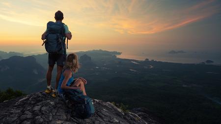 climber: Twee wandelaars op de top van de berg genieten van zonsopgang boven de tropische vallei Stockfoto