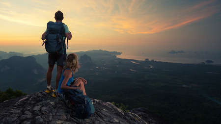 climber: Two hikers on top of the mountain enjoying sunrise over the tropical valley
