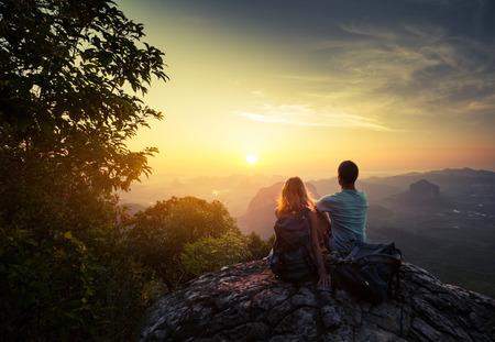 Dois caminhantes no topo da montanha que aprecia o nascer do sol sobre o vale tropical