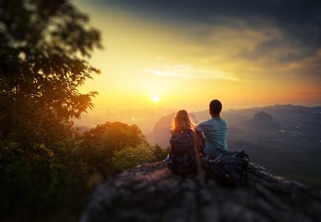 サンライズ トロピカル渓谷を楽しむ山の上に 2 つのハイカー。