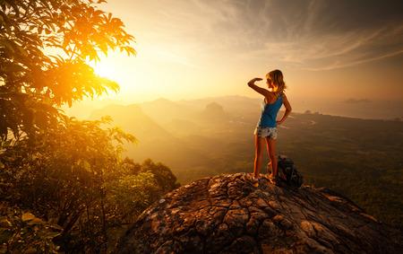 日の出の時に山の頂上に女性ハイカー