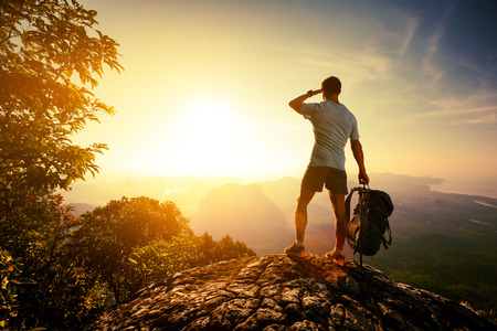 Hiker on top of the mountain enjoying sunrise over the tropical valley