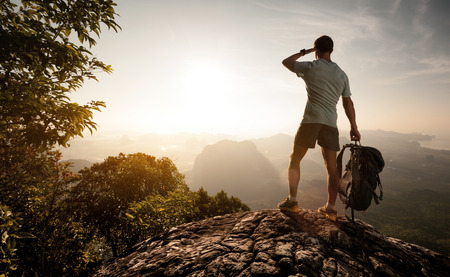 travel destinations: Hiker on top of the mountain enjoying sunrise over the tropical valley