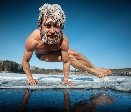 wild hair: Man with frozen hair doing yoga exercise, parsva bakasana, on the ice Stock Photo