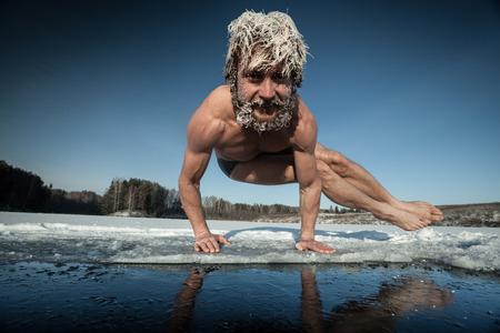 jezior: Człowiek z mrożonej włosów robi ćwiczenia jogi, Parśwa Bakasana, na lodzie Zdjęcie Seryjne