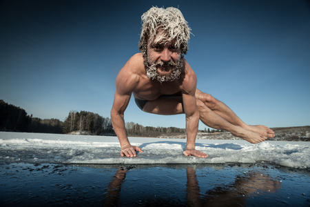 frozen lake: Man with frozen hair doing yoga exercise, parsva bakasana, on the ice Stock Photo