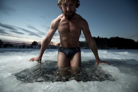 レクリエーションを持つ若い男が氷の穴で泳ぐ