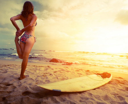 Lady surfer on the beach Stock Photo
