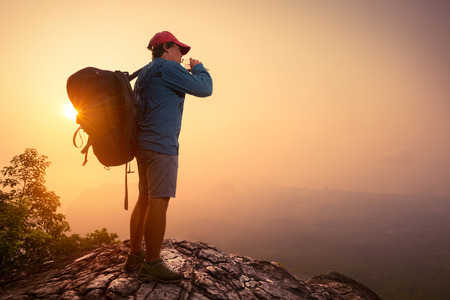 cliff edge: Hiker with backpack drinking water on top of the mountain. Stock Photo