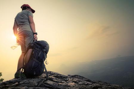 Caminhante que está no topo da montanha com trouxa