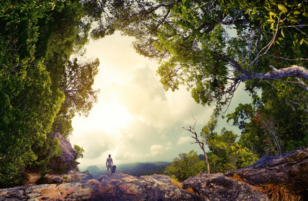 green forest: Hiker with backpack standing on the rock surrounded by lush tropical forest Stock Photo