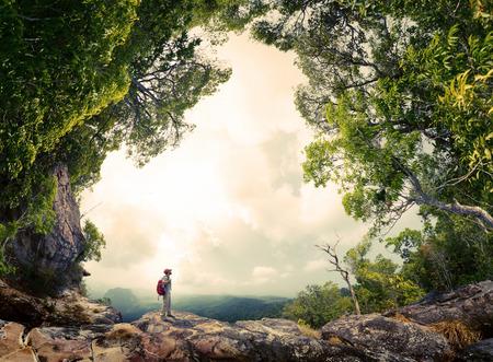 mochila: Caminante con mochila de pie sobre la roca rodeada de exuberante bosque tropical