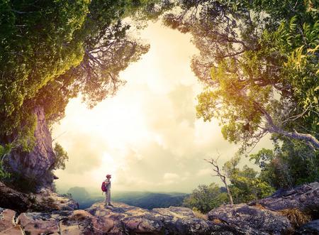 무성한 열대 숲으로 둘러싸인 바위에 배낭 서 등산객