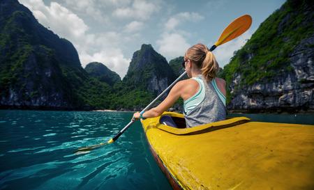 ocean kayak: Mujer explorar tranquila bah�a tropical con monta�as de piedra caliza en kayak. Ha Long Bay Vietnam