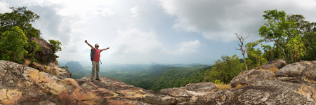 cliff edge: Hiker with backpack standing on top of the mountain with raised hands Stock Photo