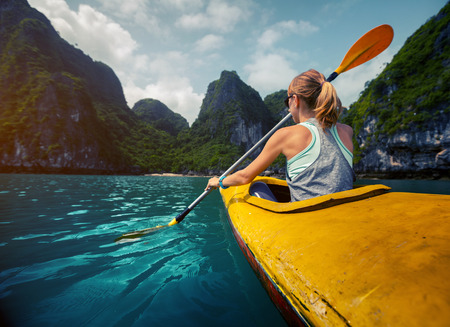 Woman exploring calm tropical bay with limestone mountains by kayak. Ha Long Bay Vietnam Stockfoto